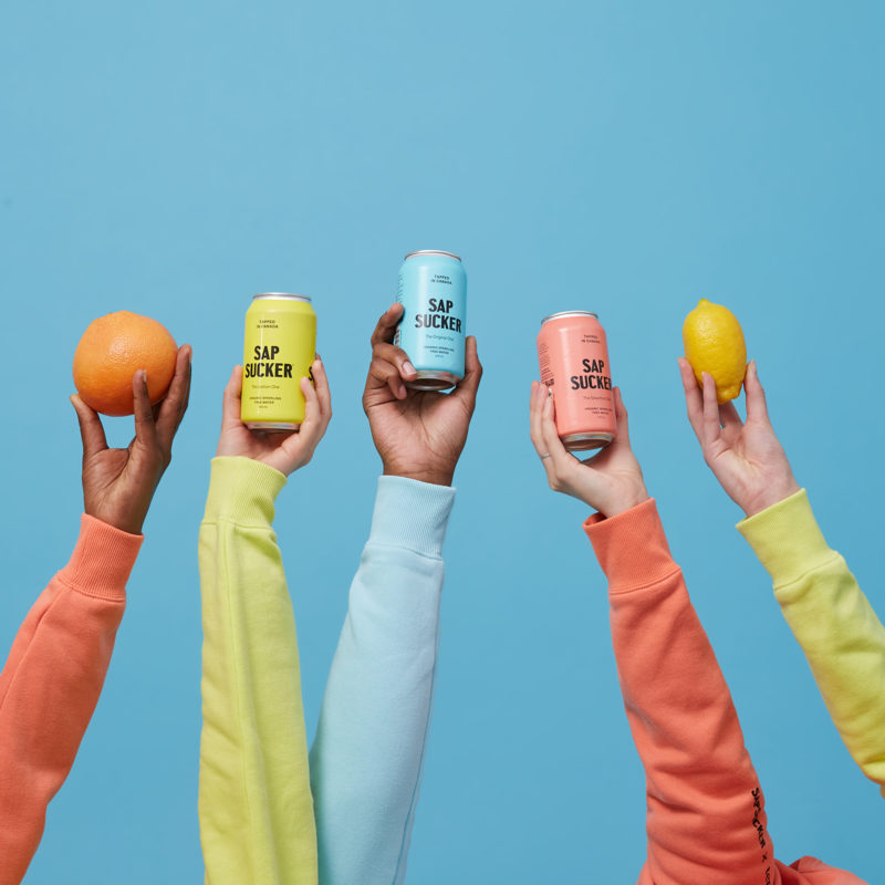 people holding coloured cans