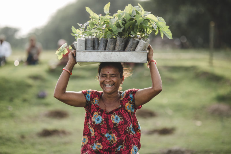 woman smiling with seedling box